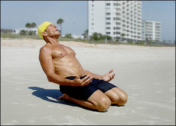 Dr. Wayne 'Mango Man' Pickering stretches during a morning workout at Ormond Beach, Fla., near Daytona.